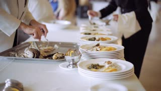 Chef's assistants helping with gourmet menu for a wedding occasion. Catering. exquisite serving dinner. a lot of white plates with vegetables, potatoes and fish. 4K (UHD).