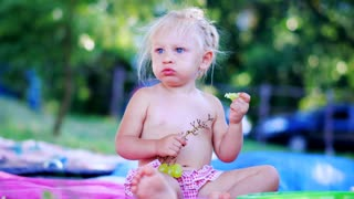 Child Eating Fruits. Beautyful Little Girl Eats Grapes in the park on the family picnic. Healthy eating concept.