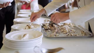 Classic catering event taking place in restaurant. Chef's assistants helping with gourmet menu for party. Waiters putting fragrant potatoes with vegetables on the plates with fish. 4K (UHD).