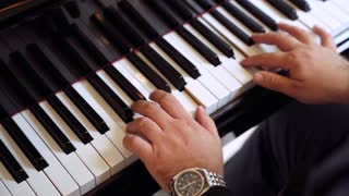 Close up hands of man playing a keyboard instrument. Male playing music on piano. 4K (UHD).