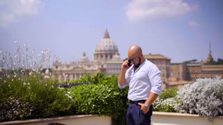Communication and people concept - young man in sunglasses using smartphone standing on the terrace in Rome in the Italian city landscape overlooking the Vatican