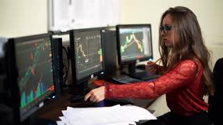 Company worker on the background of monitors in office. World financial trading. Woman calling and checking data of stock market. Shot in 4K (UHD).