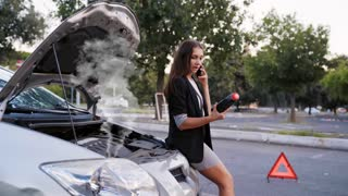Female with broken down smoking car holds a bottle with a coolant for the motor in his hand. Pretty woman talking by phone after car incident. 4K UHD video.