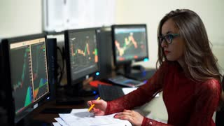 Financial trader working in office filled with computers conducting speaks on the phone when trading on the world financial market trades and analyzing currency growth.