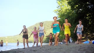 Friends having fun running down the beach. Group of happy girls jumping and have fun spending time in the Beach party. Summer vacation. Slow motion 100fps.