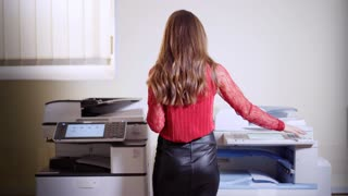 Girl printing in the office. Young beautiful woman making copies of files in the copy machine. Assistant manager working at the office.