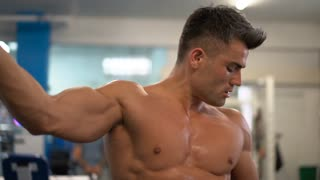 Handsome model male doing gym workout. Young man showing his strong biceps and muscular body