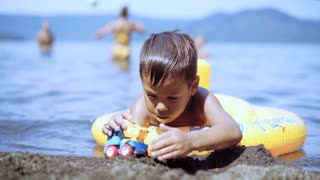 Happy child playing with toy car in water on the Sea. Family beach vacation. Young boy swimming on water on the inflatable ring in summer time.