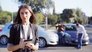 Insurance agent and the people which inspecting car accident standing on the road near damaged cars. Insurance concept. 4K UHD.