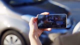 Insurance agent taking photo of car accident on the smartphone. Two broken cars after car accident standing on the road. Close-Up. 4K UHD.