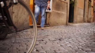 Italian lifestyle and Italian culture. An old Italian woman goes out of the market with products that carry their bike on the trunk. It runs along narrow streets with a pavement. Around her are people