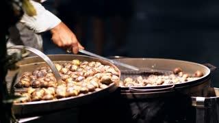 Italian street fast food. A street vendor sells roasted chestnut in night time . Baked chestnut at sale. 4K (UHD).