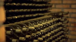 Italy wine bottles without label on the shelf inside a cellar.