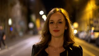 Lifestyle portrait of young attractive woman walking in city at night. People commuting background.