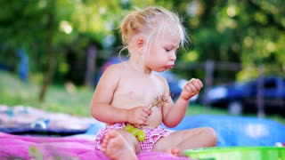 Little girl eating fresh grapes and lookind at the camera. Cute kid Eats Fruits outdoors.