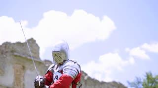 Male in armor, medieval warrior preparing for battle, historical reenactment