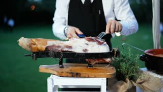 Man caterer slicing ham for the buffet in event party. Caterer, food service worker. 4K
