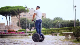 Man riding a segway. Tourist on Segway travel in the street in the city near the beautiful old buildings. Modern vehicles eco-friendly transport. Shot in 4K (UHD).