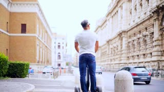 Man riding a segway, Tourist on Segway travel in the street in the city near the beautiful old buildings. Slow motion 100fps