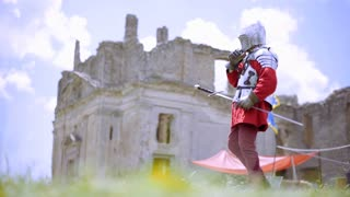 Medieval knight's in armor on the background castle.