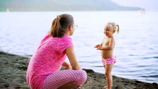 Mother and daughter standing on the shore of the lake. Mom plays with the baby outdoors.