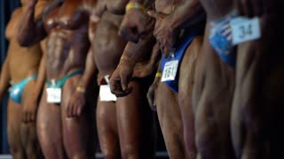 Muscular male bodybuilders posing at a sporting event in bodybuilding. Sport competition