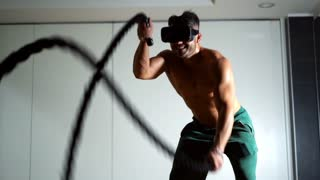 Muscular man doing battle rope exercise in a crossfit workout at the gym with virtual reality simulator on his head. VR futuristic high-tech concept of sports. Slow motion 100fps.