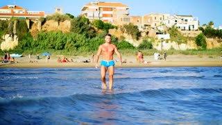 Muscular man on the beach, comes to sea and swims. Man in water. Travel and summer vacations concept. 4K