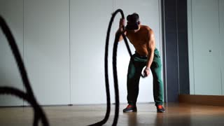 Muscular man with virtual reality glasses doing battle rope exercise in a crossfit workout at the gym. VR futuristic high-tech simulator of sports. Slow motion 100fps