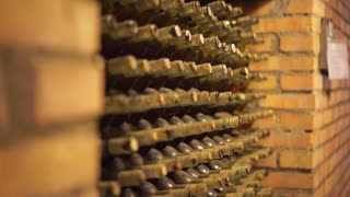 Old and dusty wine bottles in a wine cellar. Production of wine. Dark cellars with collectible red wine. 4K (UHD).