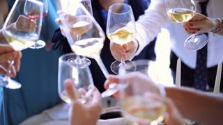 People clink glasses in a restaurant. Group of people toasting and drinking champagne. Birthday. Friends drinking Wine. 4K (UHD).