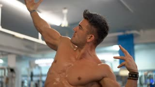 Perspiring man demonstrating his muscular body after exhausting training. Athlete man at the gym