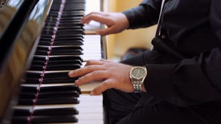 Piano music. Pianist hands playing on the Grand Piano in the at a classical music concert. Musician of the Orchestra. Shot in 4K (UHD).