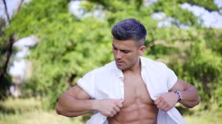 Portrait of Handsome Muscular athlete which enjoying nature outdoors in hot summer's day in the city park. Model man Tourist.