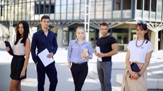 Portrait of young diverse business team near office. A group of business people stand together with serious look.