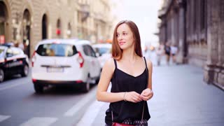 Portrait of Young tourist woman in Rome during summer italian vacation. On the background the People walk and movement of cars on the streets of Rome Italy. Italian style of life.