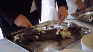 Professional chefs peeling slowly sea fish prepared before it and putting on the plates for further service. Catering food and service is of high quality. 4K (UHD).