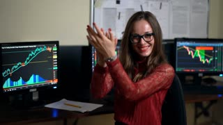 Professional female financial trader forex in modern office filled with computers. Businesswoman trader satisfied with successful bidding the world markets.