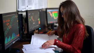 Professional financial trader working in modern office filled with computers conducting trades and analyzing currency growth. Young business woman is analyzes informations the world markets.
