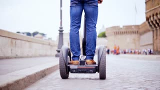 Riding segway in the street of city. Driving a personal transporter while visiting city. Slow motion 100fps