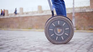 ROME, ITALY - MAR 01, 2018:  A young guy rides on a segway in a circle, a close-up of the wheels. Scooter goes in the circle.