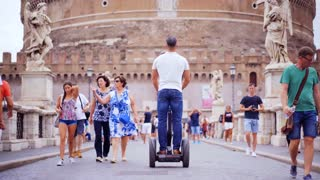 ROME, ITALY - MAR 01, 2018: Happy tourist riding on segway on the background of the sant'angelo castle, this is a famous tourist spot in Rome. Italian tourism.