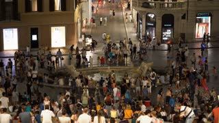 ROME, ITALY - SEPTEMBER 2018: The crowds of tourists sit on the Spanish stairs and walk around the fountain over the square of Piazza di Spagna at summer night time.