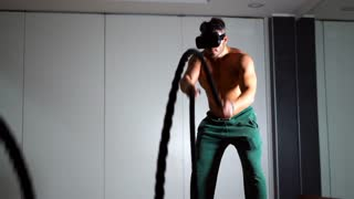 Shirtless sportsman using virtual reality technology for training. Man actively working out using the ropes at a gym. Cross fitness workout. VR and sport concept. 4K UHD.