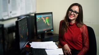 Smiling financial trader working in office. Successful advisor on the background of diagrams. World market and sales statistics. Shot in 4K (UHD).