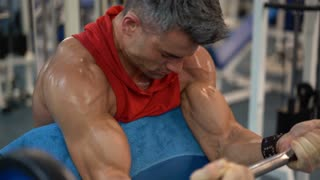 Sports bodybuilder young man hard training biceps muscles in gym
