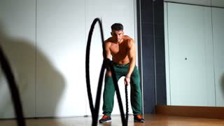 Sportsman doing battle rope exercise in a crossfit workout at the gym. High-intensity interval training. Exercise / fitness. Muscular male. Slow motion 100FPS.