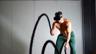 Sportsman using virtual reality technology during a training session at the gym. Sport and virtual reality concept. Two intensity training sessions. Slow motion 100fps.