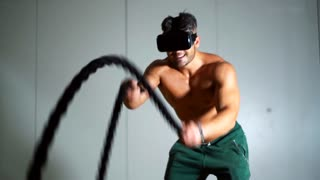Sportsman using virtual reality technology for training in gym. Man actively working out using the ropes at a gym. Cross fitness workout. VR and sport concept. 4K UHD.