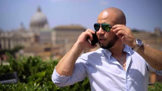 Successful businessman uses a smartphone at work. Business, technology, communication and people concept. Young man outdoors.